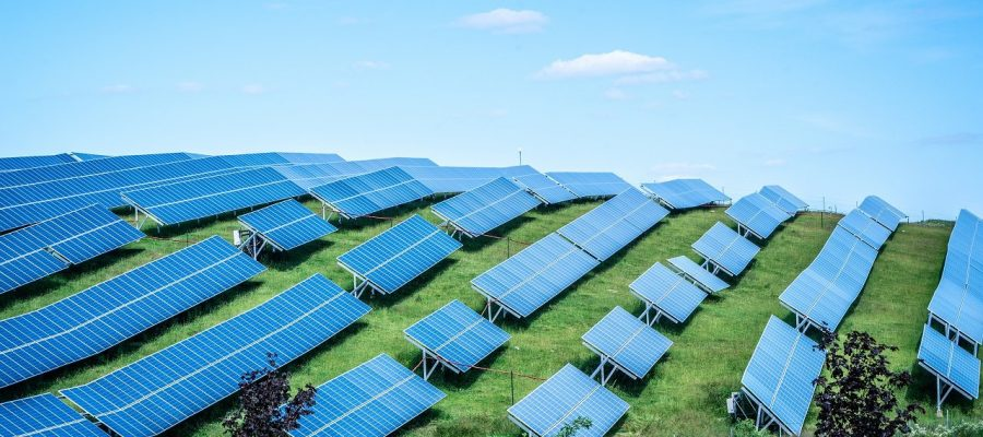 Solar panels against blue sunny sky produce green, environmentally friendly energy from sun. Blue solar panel background of photovoltaic modules for renewable energy. Copy space